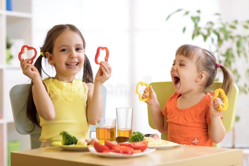 Funny children girls eating healthy food. Kids lunch at home or kindergarten. stock photos