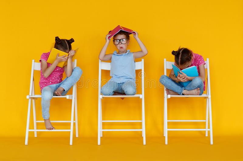 Funny children girls read books on colored yellow background royalty free stock photography