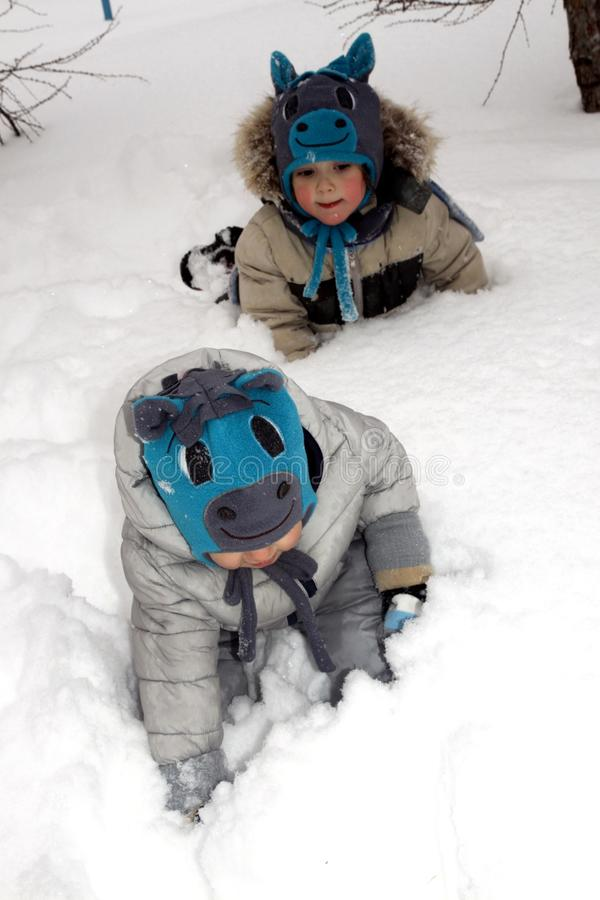 Funny children in hats in the form of a horse on a walk in the park stuck in snowdrifts royalty free stock photos