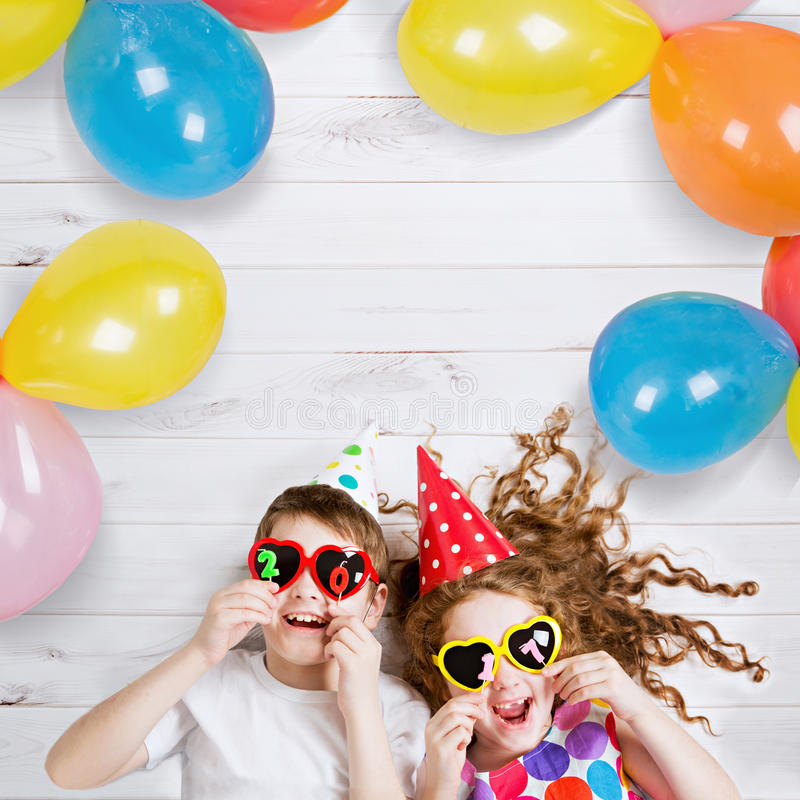 Funny children hold 2017 shaped candles lies on the wooden floor. New Years 2017, christmas holiday. Funny children with sunglasses, hold 2017 candles, lies on stock images