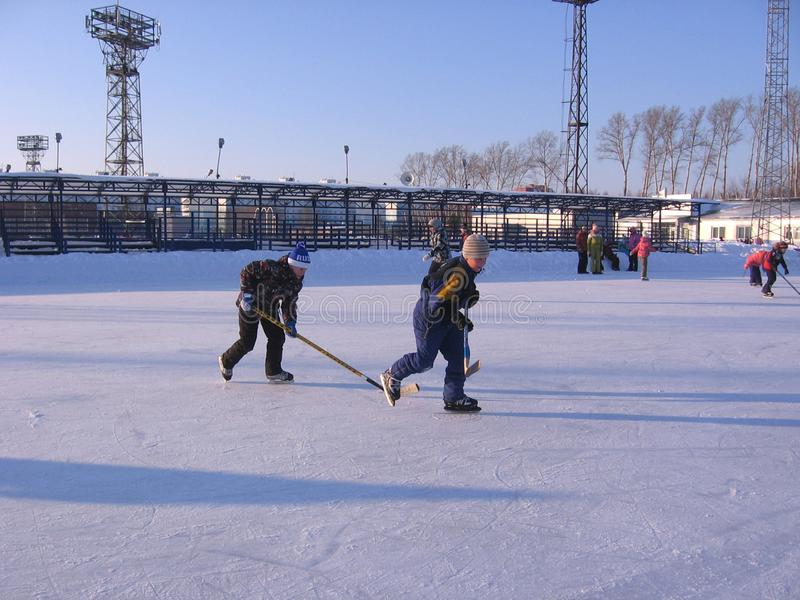 Funny children at the rink in winter skate playing hockey royalty free stock image