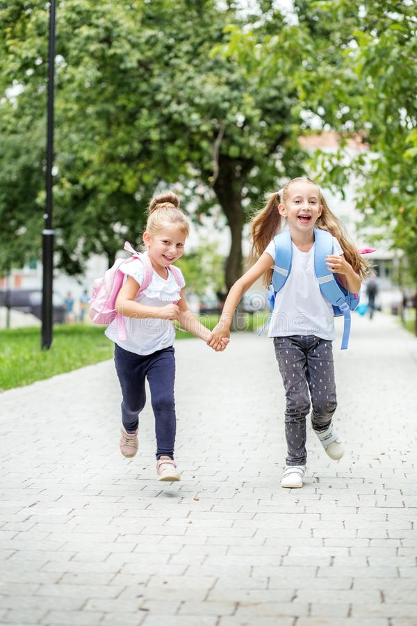 Funny children run from school with backpacks. The concept of school, study, education, friendship, childhood. Funny children run from school with backpacks royalty free stock photography