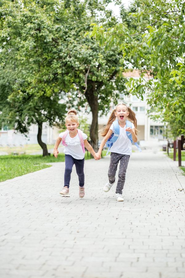 Funny children are running from school. The concept of school, study, education, friendship, childhood. Funny children are running from school. The concept of royalty free stock photography
