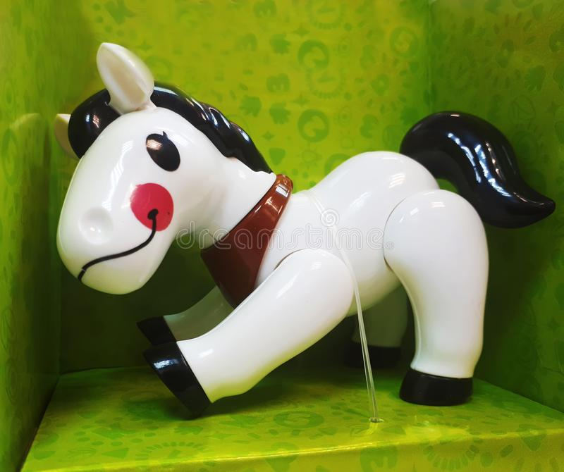 Funny children`s toy for the baby - a white horse with black in a green box. horizontal photo.  stock photo