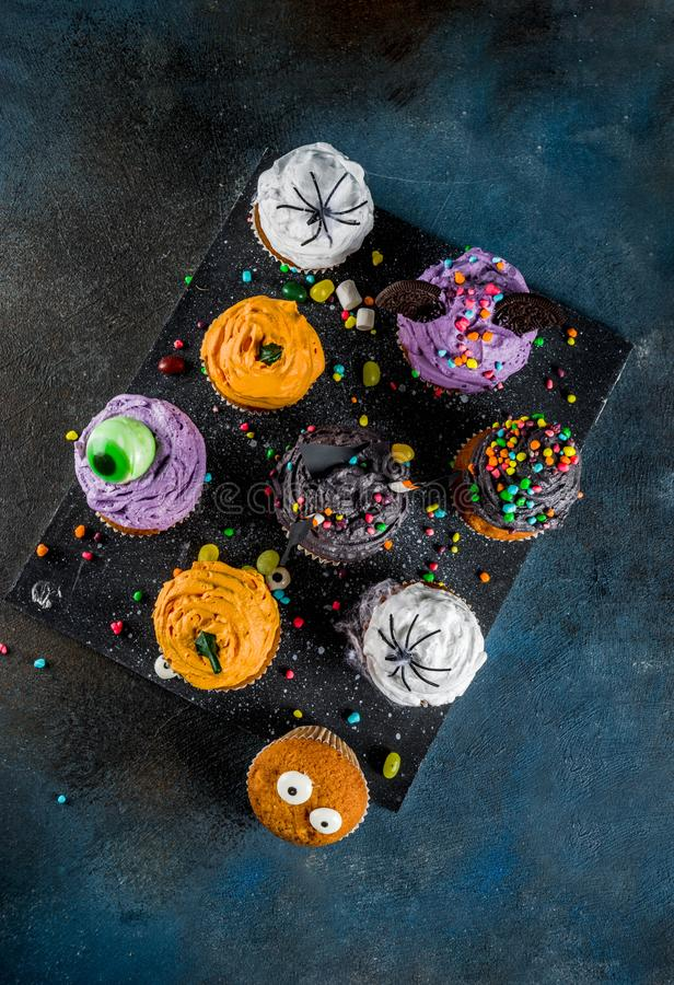 Funny children`s treats for Halloween. Variations of cupcakes, decorated in the form of different monsters, witches, pumpkins, ghosts. Dark rusty blue stock photo