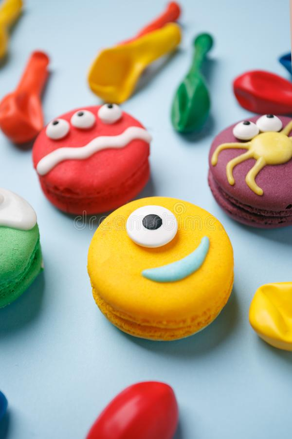 Funny children`s treats for Halloween: variations of macaroon, decorated in the form of different monsters, ghosts. Cooking proce royalty free stock photography