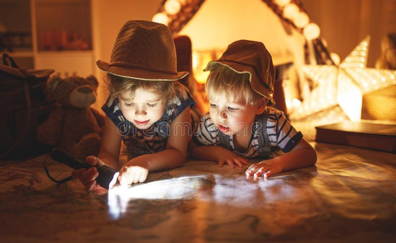 Funny children tourist with flashlight and world map and backp stock photos