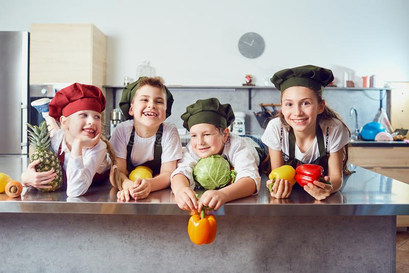 Funny children in the uniform of cooks on the table in vegetable royalty free stock photography