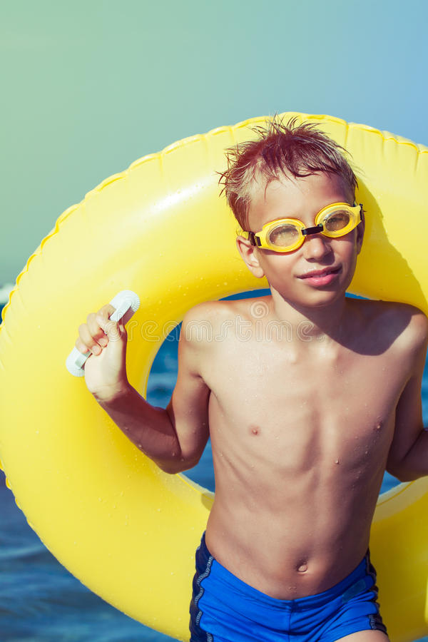 Funny chilld with swimmer goggles standing on beach stock photo