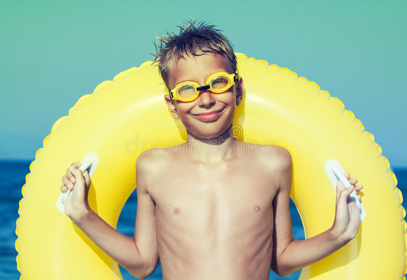 Funny chilld with swimmer goggles standing on beach royalty free stock photo