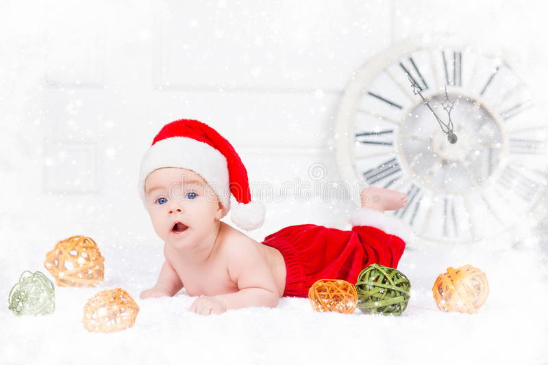 Funny Christmas baby in Santa Claus costume lying on white background stock photos