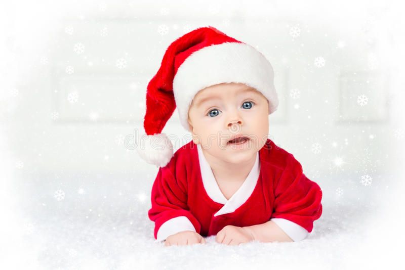 Funny Christmas baby in Santa Claus costume lying on white background stock photo
