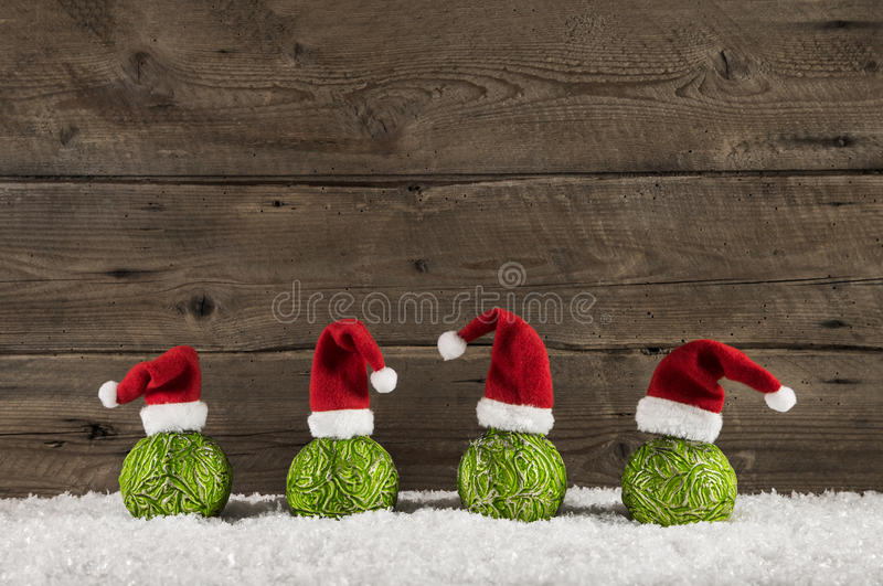 Funny christmas background with green balls and santa hats on wood. royalty free stock photo