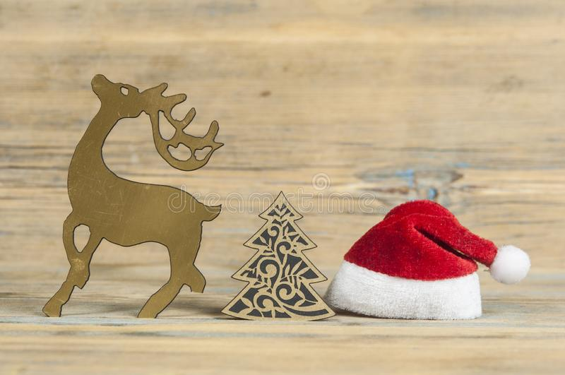 Funny christmas card with reindeer wearing a santa hat for a greetings on a wooden background. Christmas reindeer with santa hat in festive setting stock photography