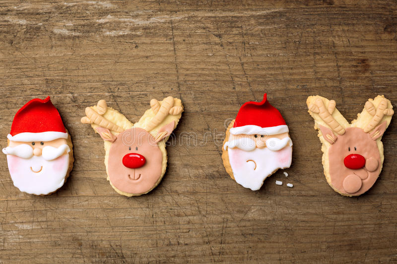 Funny christmas cookies santa and reindeer on wood background royalty free stock photography