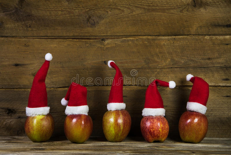 Funny christmas greeting card with five red santa hats on apples stock image
