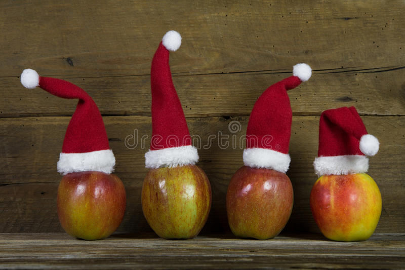 Funny christmas greeting card with four red santa hats on apple. Decoration: Funny christmas greeting card with four red santa hats on apples with wooden stock photos