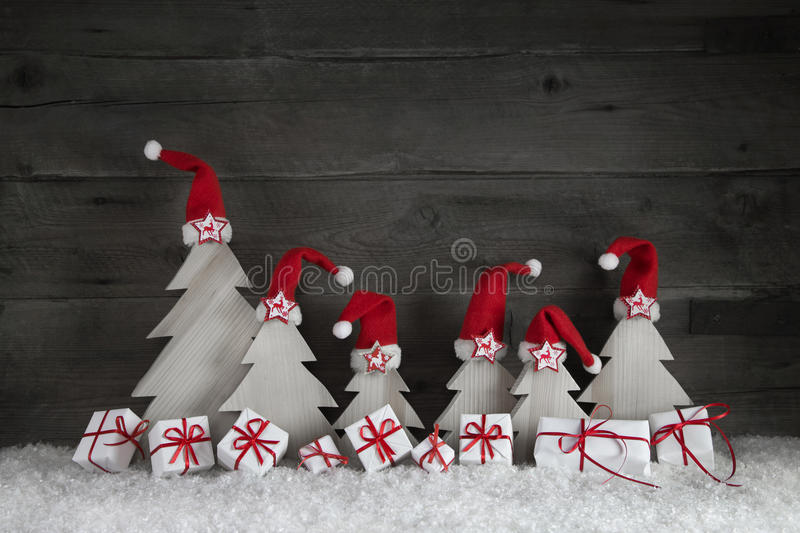 Funny christmas trees with santa hats and gift boxes on wooden b. Funny christmas trees with santa hats and presents on wooden background with red ribbon and stock images