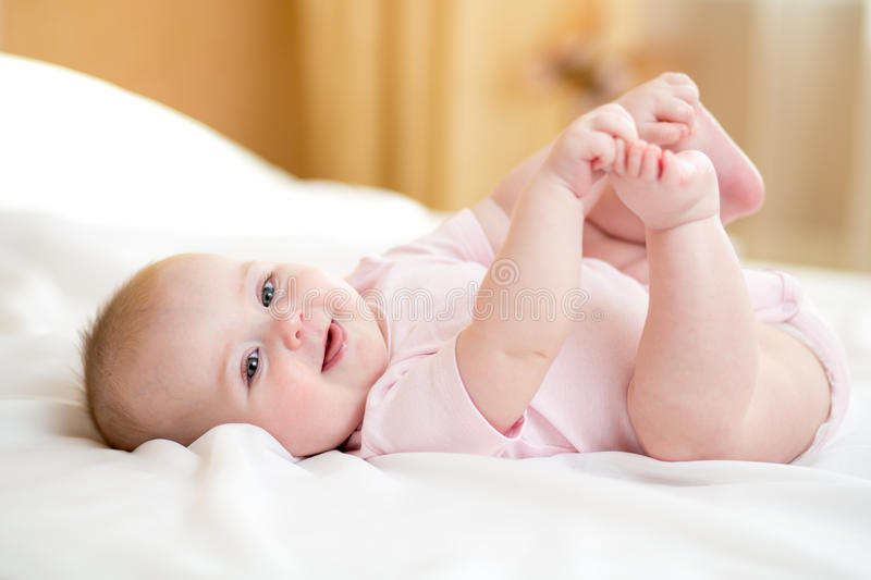 Funny chubby baby infant girl playing with her feet. Funny chubby baby infant girl playing with feet royalty free stock photography