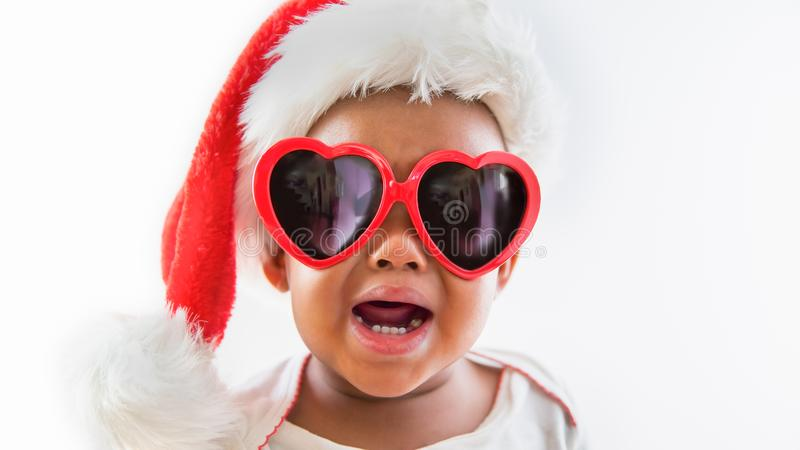 Funny portrait of naughty African American Baby wearing Sunglasses and Santa Hat Screaming Crying royalty free stock image