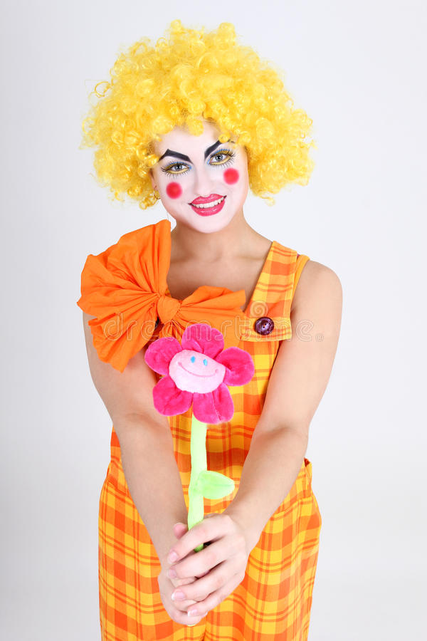 Funny clown with colourful flower. Funny clown in costume with colourful flower stock images