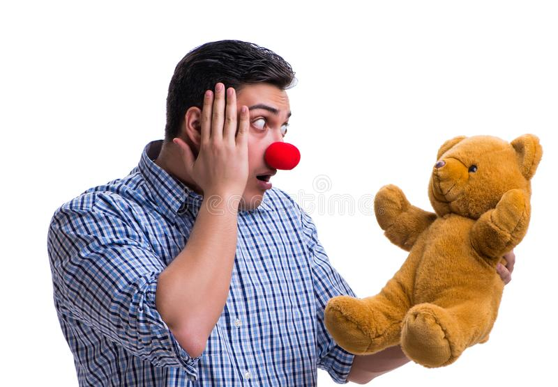 Funny clown man with a soft teddy bear toy isolated on white bac. Kground royalty free stock image
