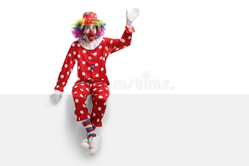 Funny clown sitting on a white panel and waving stock photo