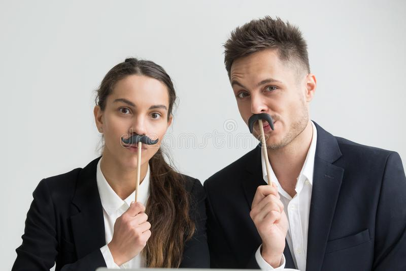 Funny colleagues making silly faces holding fake mustache, heads. Funny male and female colleagues in suits holding fake mustache, businessman and businesswoman royalty free stock images