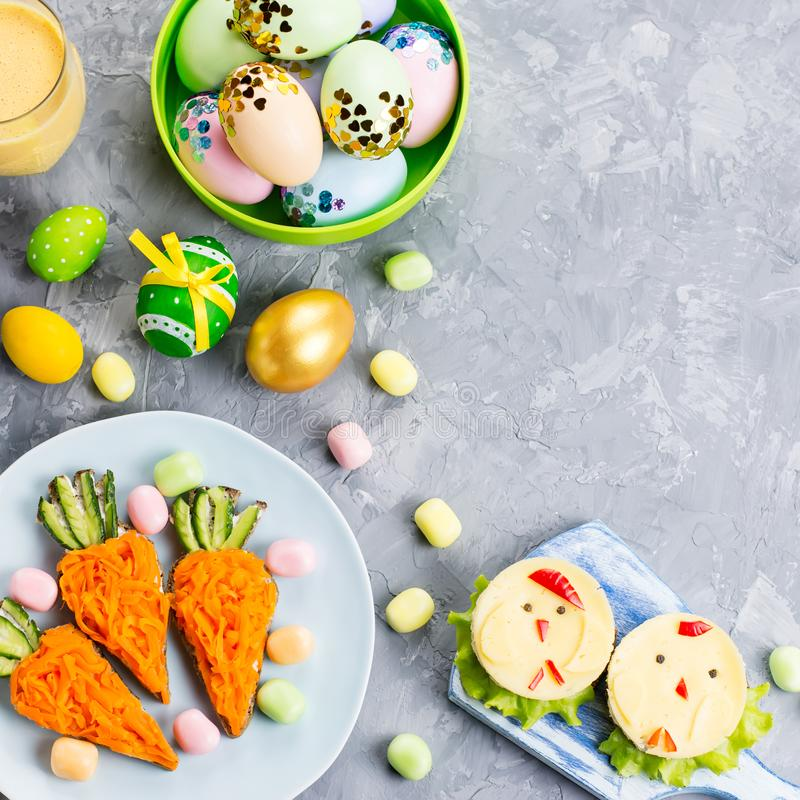 Funny colorful Easter food for kids with decorations on table. Easter dinner concept stock image