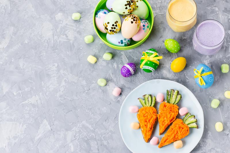 Funny colorful Easter food for kids with decorations on table. Easter dinner concept. Top view stock photo
