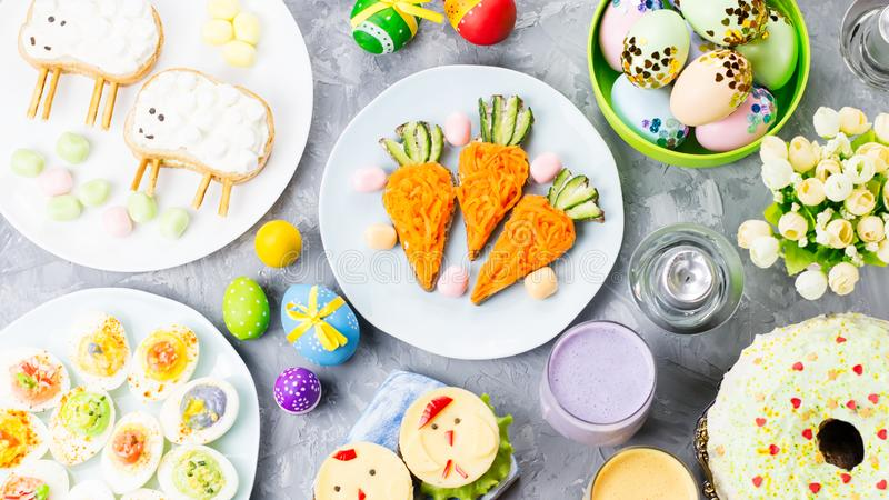 Funny colorful Easter food for kids with decorations on table. Easter dinner concept royalty free stock image