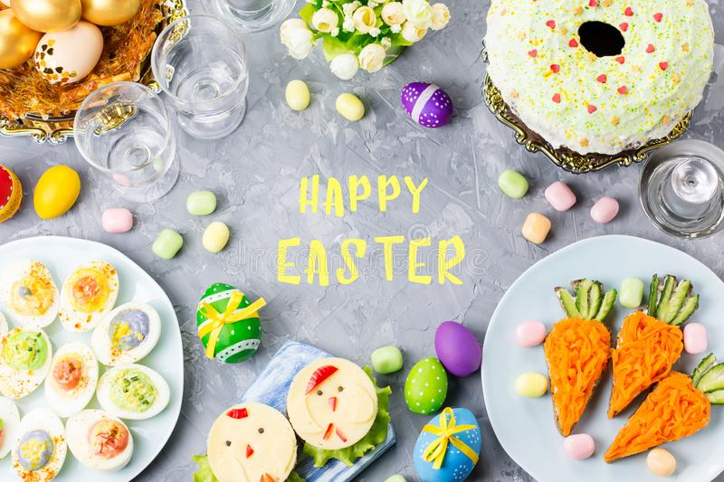 Funny colorful Easter food for kids with decorations on table. Easter dinner concept. Top view royalty free stock photography
