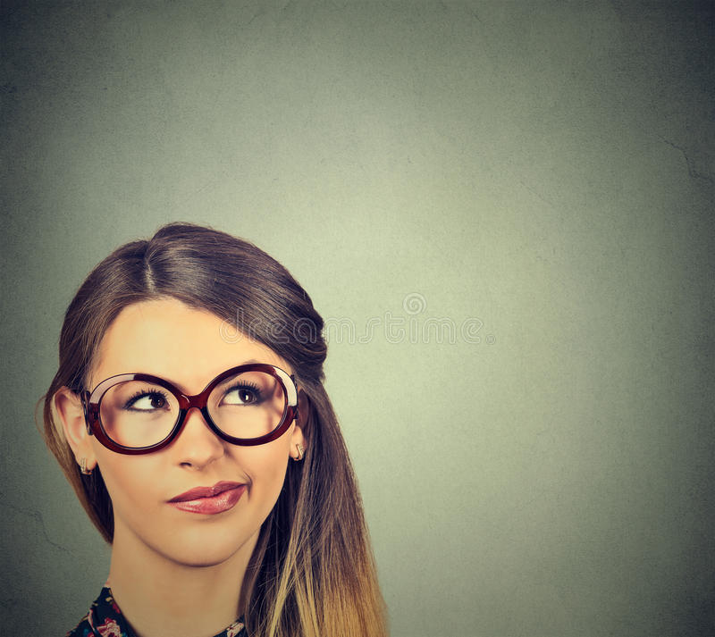 Funny confused skeptical woman in glasses thinking planning looking up. Closeup funny confused skeptical woman in glasses thinking planning looking up on gray stock photo