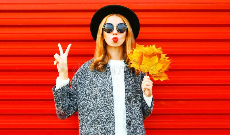 Funny cool girl with red lips and yellow maple leaves royalty free stock image