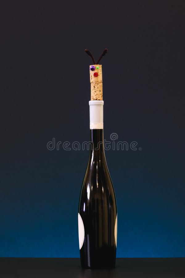 Funny cork stopper on top of wine bottle. Alcohol intoxication concept. stock photo