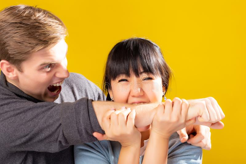 Funny couple. Asian girlfriend biting caucasian boyfriend by kidding him. Husband get shocked, surprised, scream, hurt, painful. T royalty free stock photos