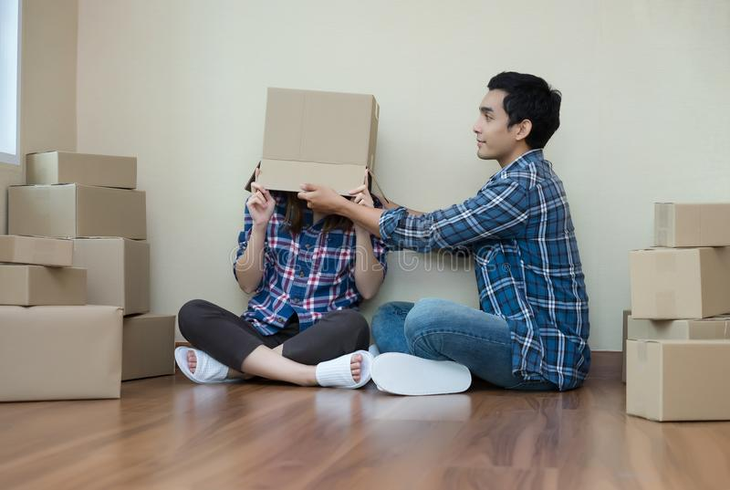 Funny couple celebrating move to new apartment, enjoy sitting on. Floor after at new home between boxes royalty free stock images