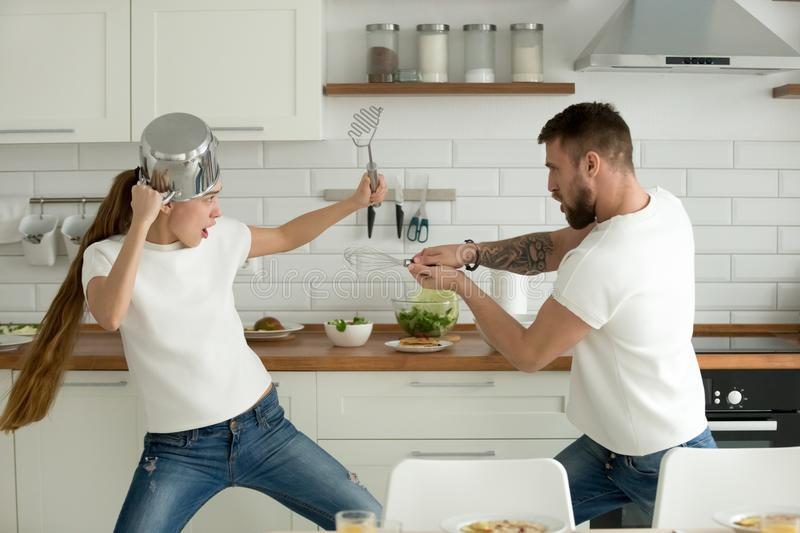 Funny couple having fun fighting with kitchen utensils cooking t royalty free stock images