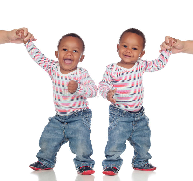 Funny couple of identical brothers learning to walk. Isolated on a white background royalty free stock photography