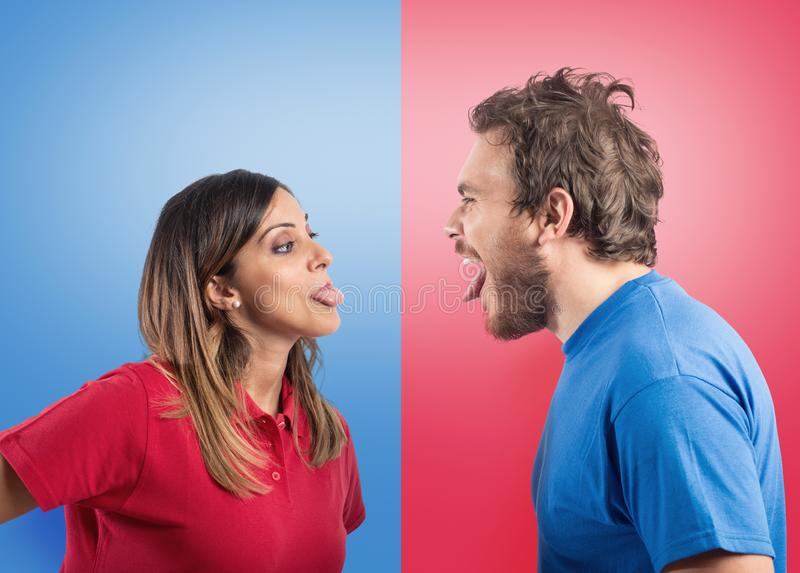 Funny couple joke with grimaces on colored background. Funny couple joke with grimaces on colored blue and red background royalty free stock photos