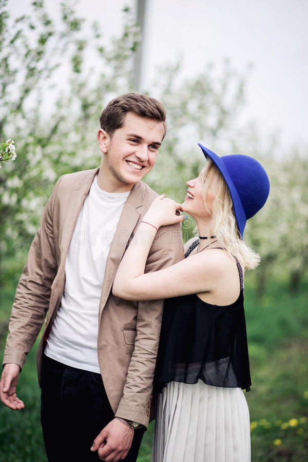 Funny couple laughing with a white perfect smile and looking each other outdoors royalty free stock photo