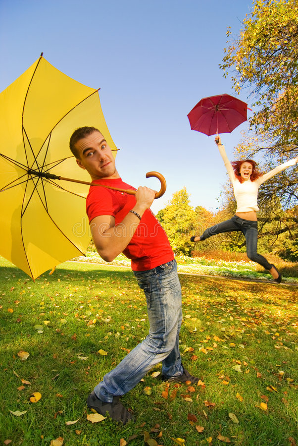 Funny couple with umbrellas. On autumn background