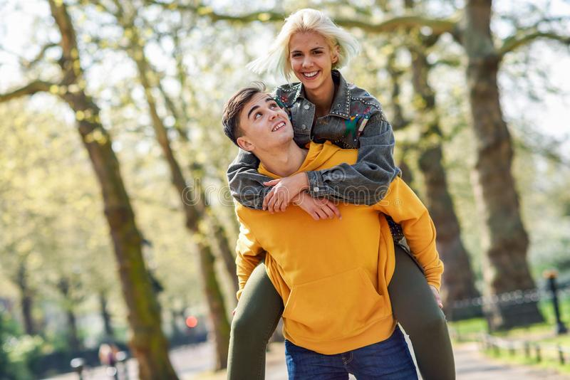 Funny couple in a urban park. Boyfriend carrying his girlfriend on piggyback. Love and tenderness, dating, romance. Lifestyle concept stock image