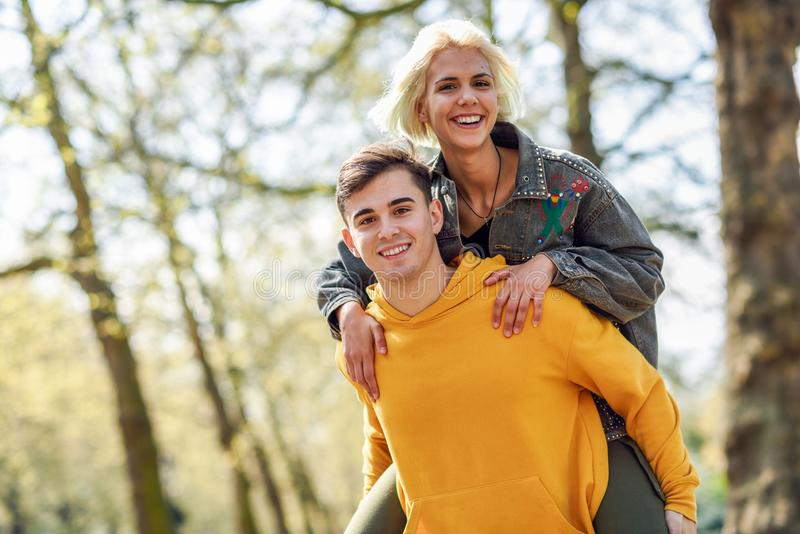 Funny couple in a urban park. Boyfriend carrying his girlfriend on piggyback. Love and tenderness, dating, romance. Lifestyle concept royalty free stock photo
