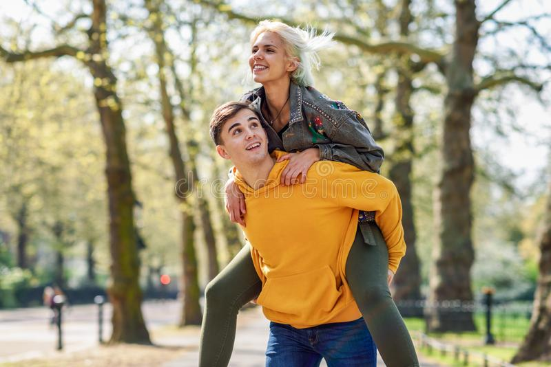 Funny couple in a urban park. Boyfriend carrying his girlfriend on piggyback. Love and tenderness, dating, romance. Lifestyle concept royalty free stock photos