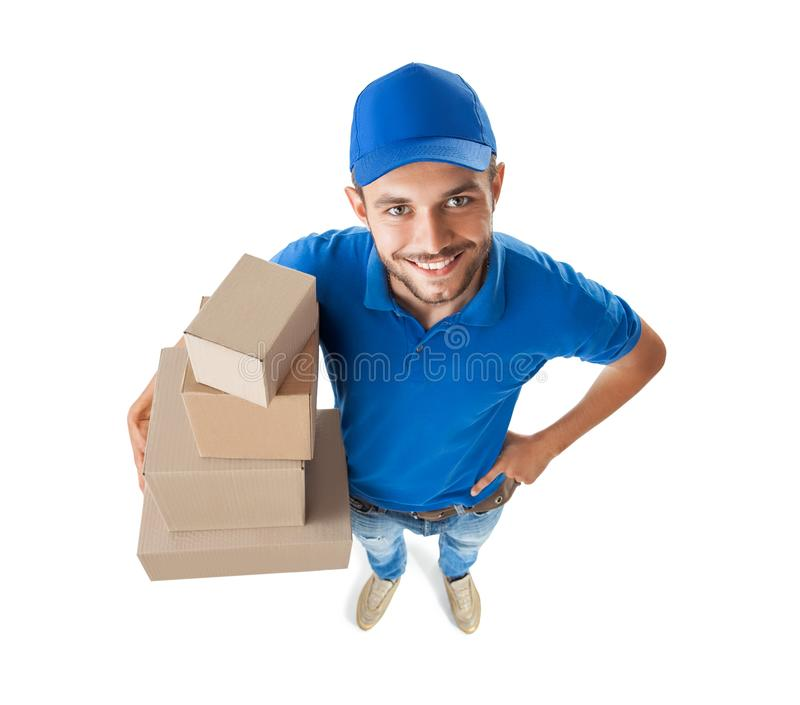 Funny courier with boxes looking at camera isolated on white background. Top view, fish eye lens shot royalty free stock photography