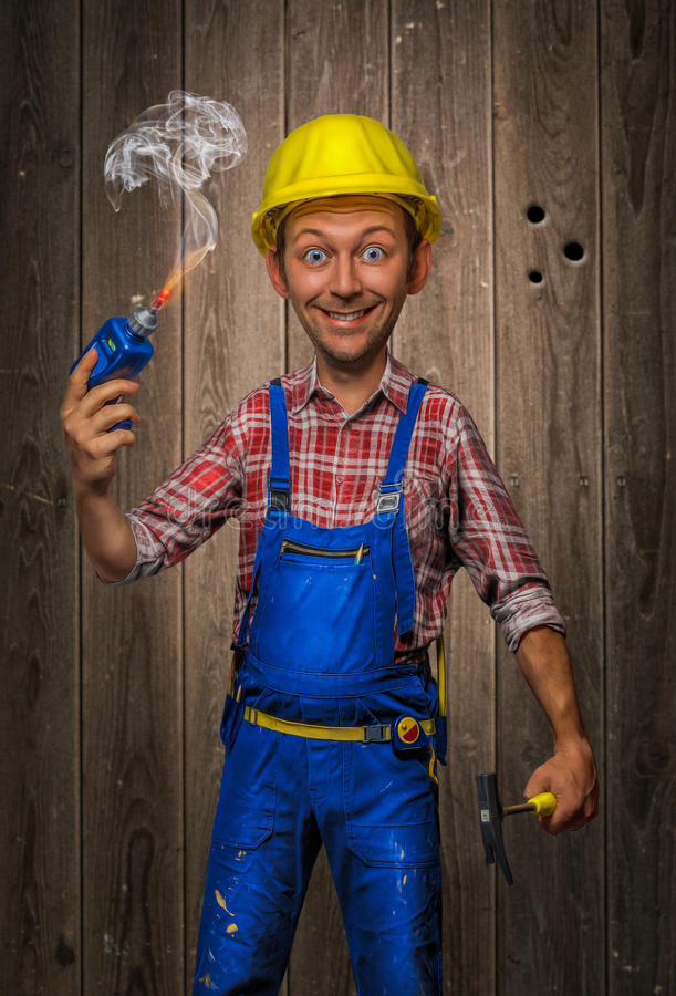 Funny Craftsman with Hammer, cordless screwdriver and helmet. At wooden background royalty free stock photos