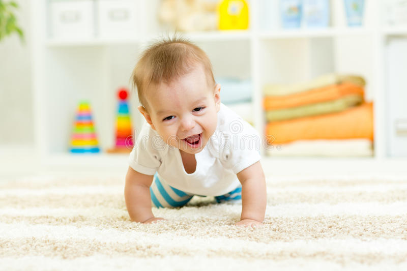 Funny crawling baby boy. Funny baby boy crawling on carpet at home royalty free stock image