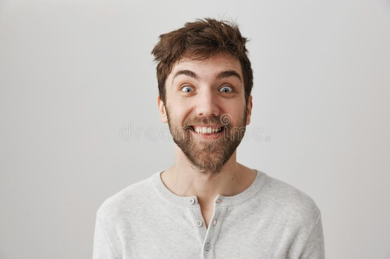 Funny and crazy bearded guy with messy hair and popped eyes, smiling and staring at camera, standing against gray. Background. Obsessed man stalks his ex royalty free stock photo