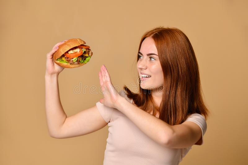 Close up portrait of a hungry young woman eating burger isolated over nude background. Funny crazy smiling Skinny ginger girl in shorts holds a burger hamburger royalty free stock images